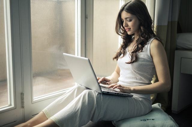 mladá žena sedí u okna a na klíně má notebook