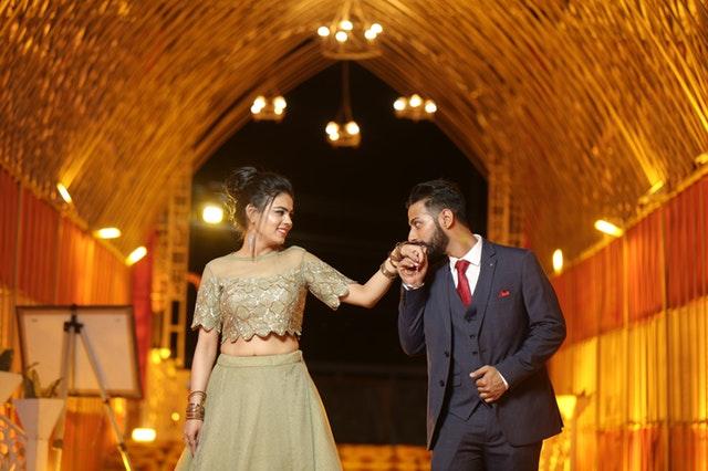 Dvojice ve společenských šatech-muž líbá ženě ruku.jpg