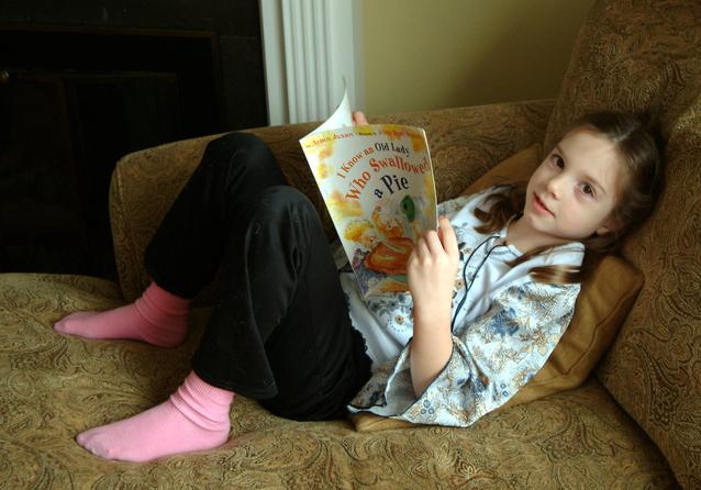 sedící dívka na pohovce při čtení.jpg